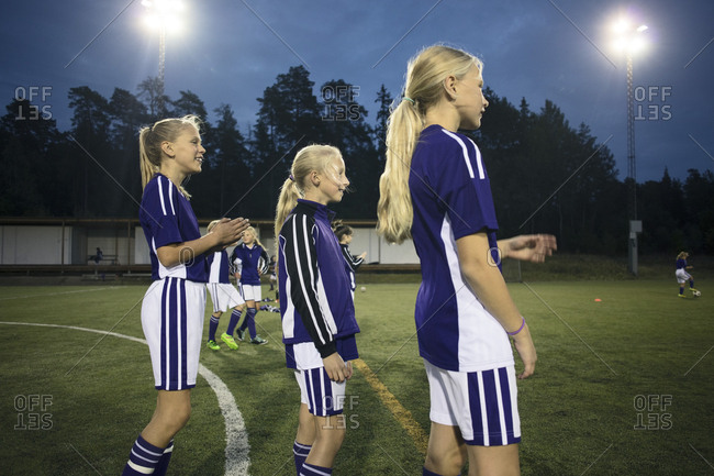 Side view of girls standing on soccer field against sky at dusk