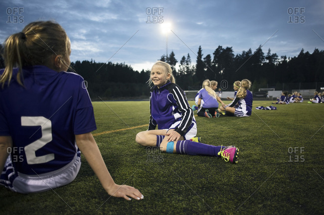 Girls relaxing on soccer field against sky