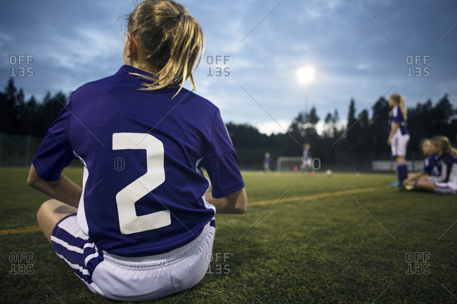 Rear view of girl sitting on field against sky