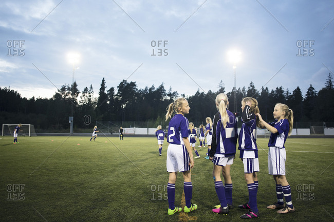 Girls standing on soccer field against sky