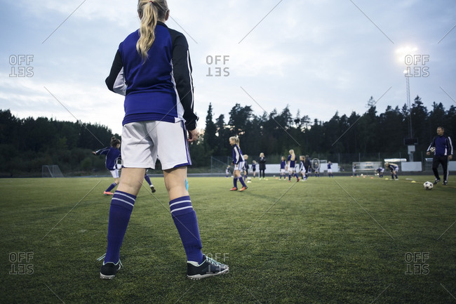 Rear view of girl looking at players playing on soccer field