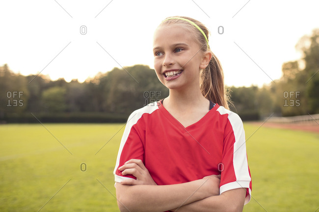Happy female athlete looking away standing with arms crossed on soccer field