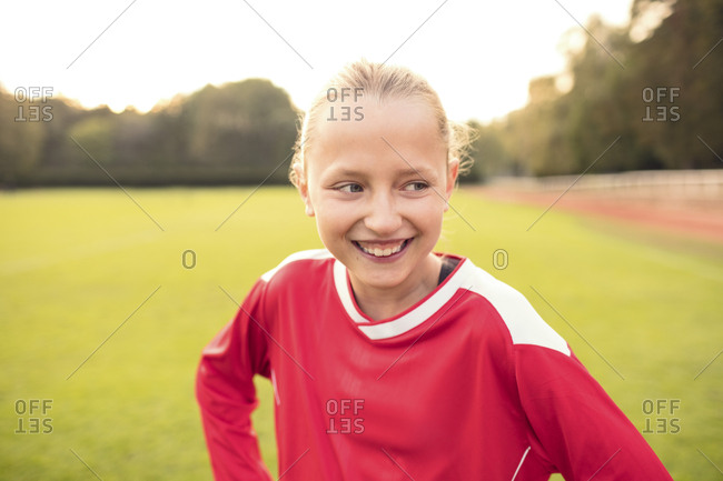 Happy soccer player looking away while standing on field