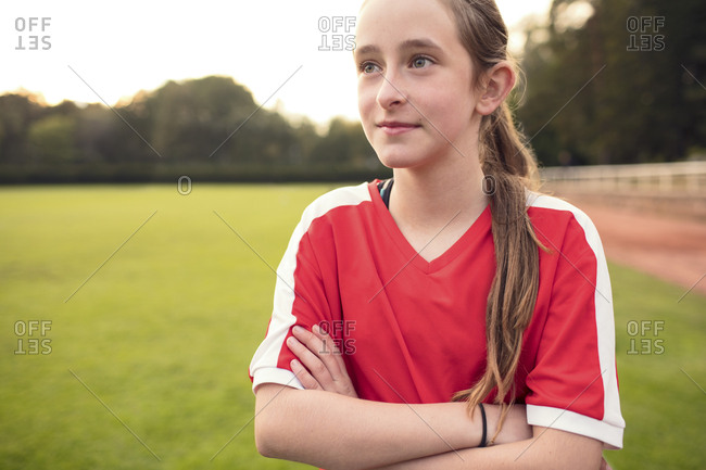 Girl standing with arms crossed on soccer field