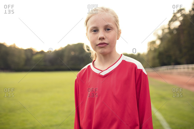 Portrait of confident female athlete standing on soccer field