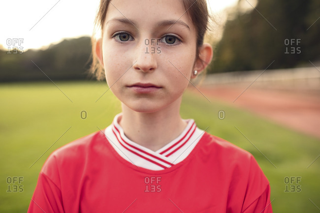 Portrait of confident female soccer player standing on field