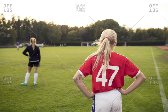 Rear view of girl standing on soccer field