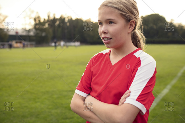 Female soccer player standing with arms crossed on field