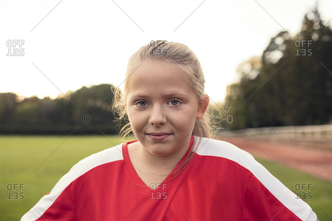Portrait of girl wearing red uniform standing on soccer field against sky