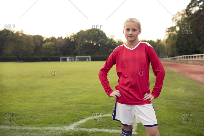 Portrait of confident girl standing on soccer field