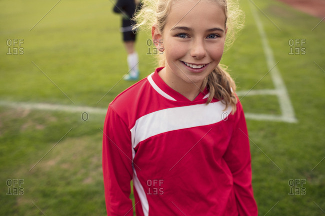 Portrait of happy girl standing on soccer field