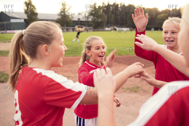 Playful female soccer players standing against field