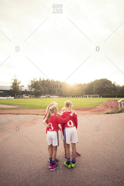 Athletes talking while standing on footpath against sky during sunset