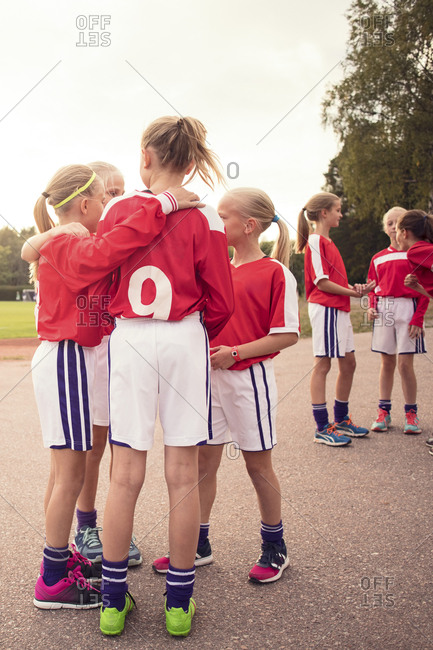 Soccer girls talking while standing on footpath against sky