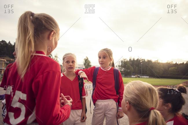 Girls wearing red soccer uniform talking against sky