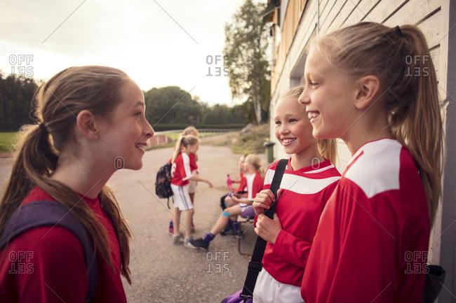Girls talking against friends by wall