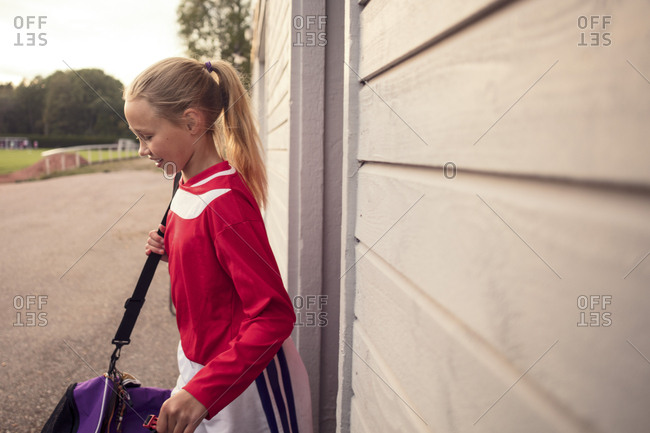 Side view of girl with bag standing by wall