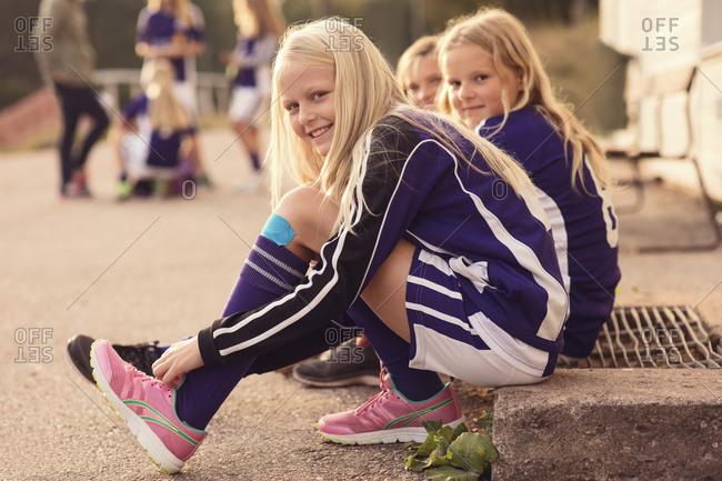 Portrait of happy girls tying shoelaces