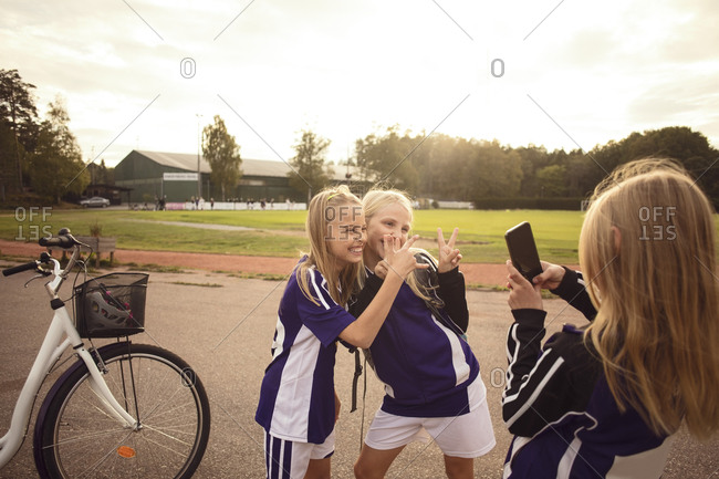 Girl photographing friends showing hand signs standing on footpath by soccer field