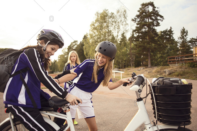Cheerful friends enjoying with bicycle on footpath