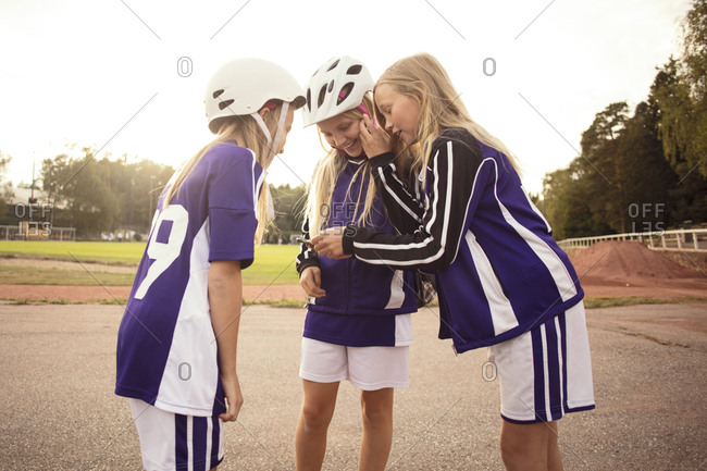 Happy female soccer players looking in mobile phone standing on footpath by soccer field