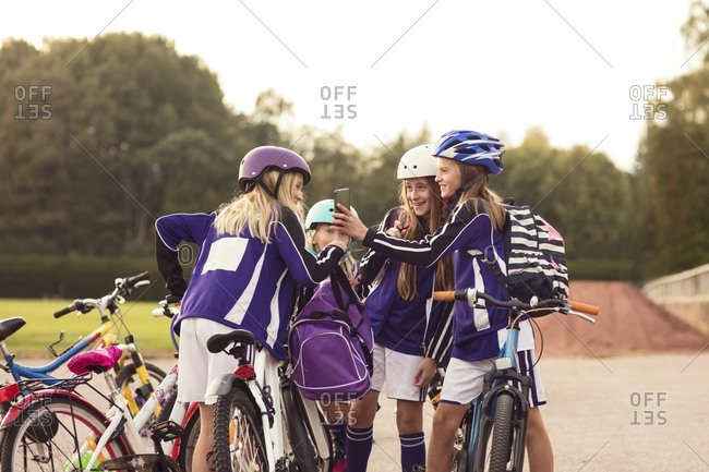 Girls showing mobile phone to friends standing with bicycles on footpath against sky