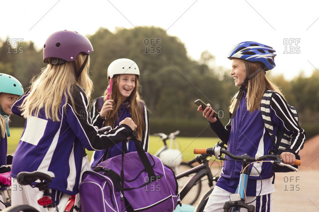 Happy girls wearing helmet standing with bicycles against sky