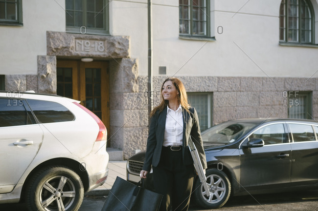 Smiling female realtor carrying signboard and bag while crossing street against cars