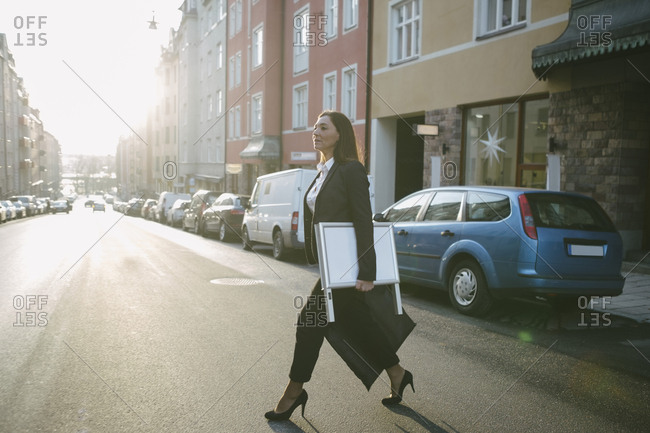 Side view of female realtor carrying signboard and bag while crossing street in city
