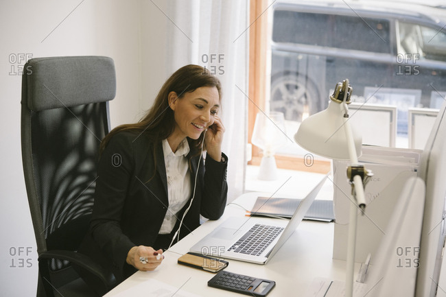 Happy realtor listening to headphones while looking at laptop in office
