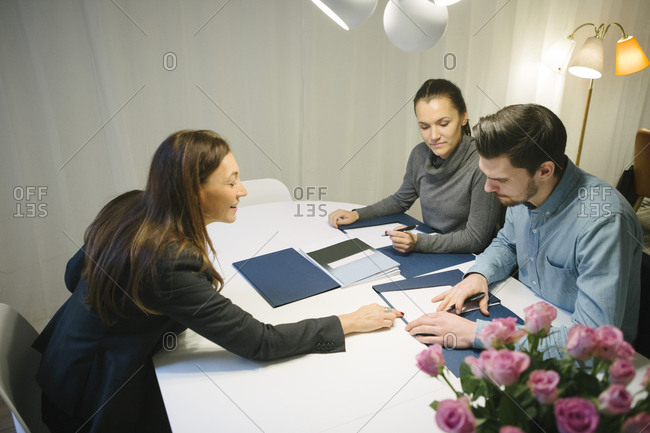 High angle view of mature female real estate agent assisting young couple with brochure at desk in office
