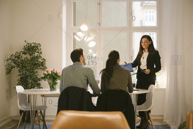 Smiling female realtor and young couple discussing at office