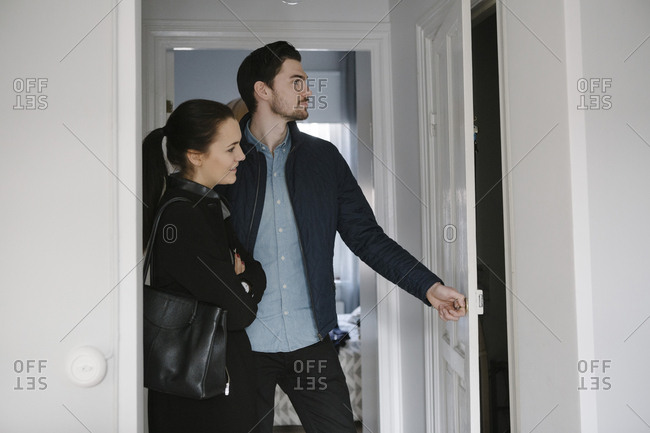Young man opening door while standing with woman in corridor at home