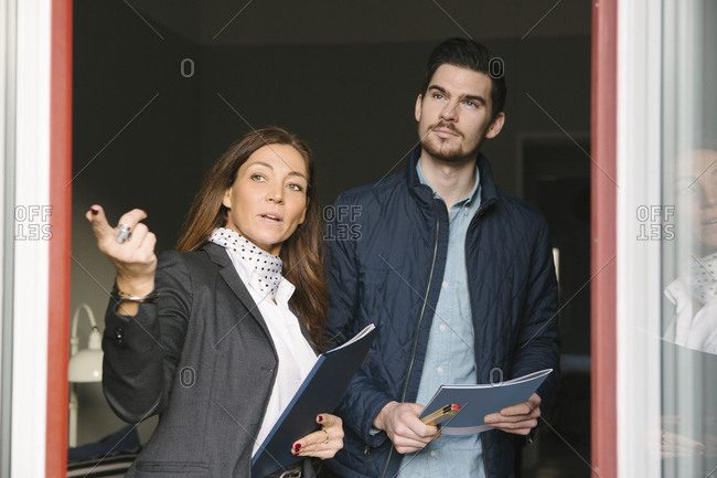 Female realtor and young man standing by window while pointing away