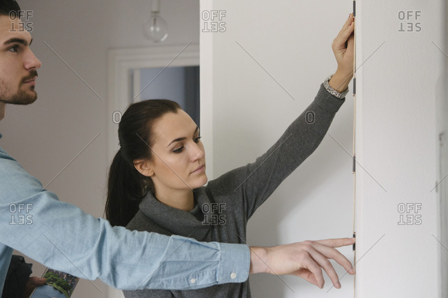 Young man standing by woman measuring white wall with tape at home