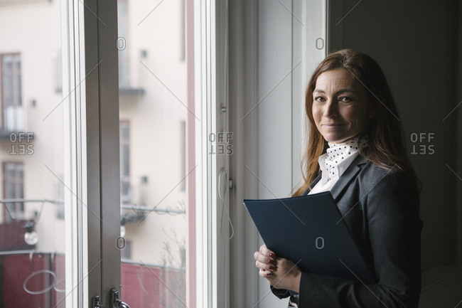 Portrait of confident mature female real estate agent standing with brochure by window at home