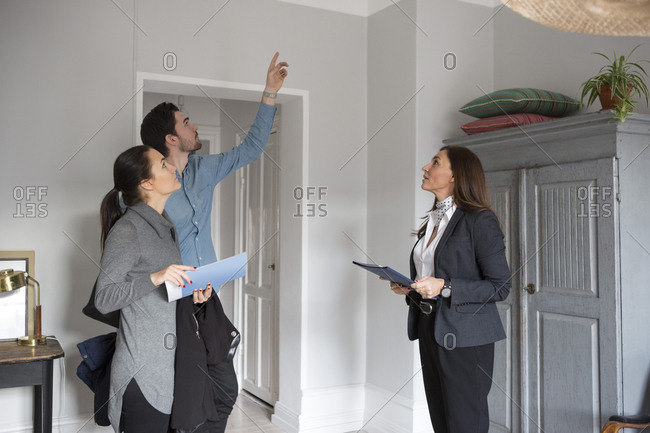Woman and female realtor looking at man pointing up while standing in room