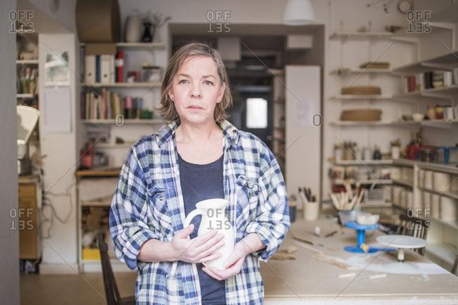 Portrait of mature female potter holding pitcher jug at workshop