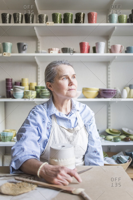 Senior female potter looking away while sitting at table with vase in workshop