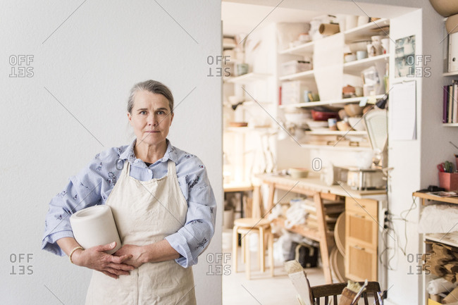 Portrait of senior female potter standing with vase against white wall at workshop