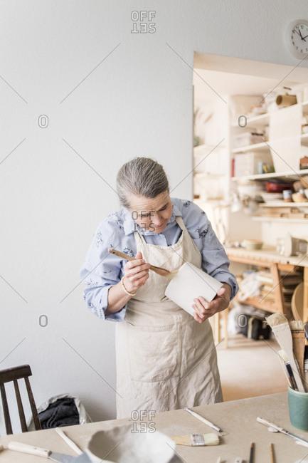 Senior female potter using paintbrush on vase by table at workshop
