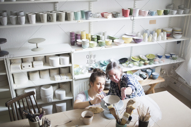 High angle view of mature female potter assisting young craftsperson in molding clay at workshop