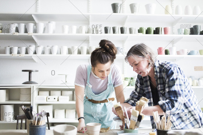 Young female potter looking at mature artist molding clay at workshop