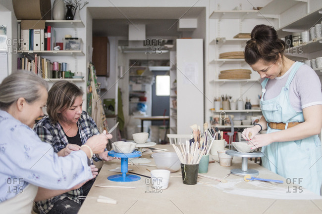 Female potters molding clay at workbench in store