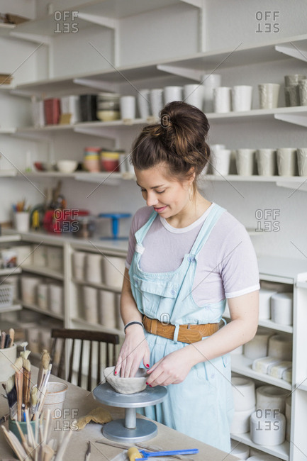 Smiling young potter molding shape on clay while standing by workbench at store