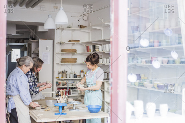 Female potters standing by table working in ceramics workshop