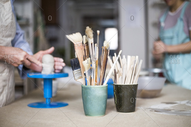 Hand tools and paintbrushes in containers on workbench with female potters working in background