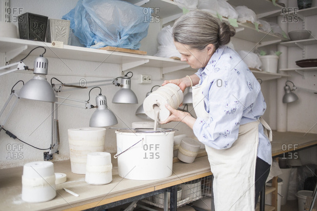 Senior female potter pouring clay from vase in bucket on workbench at workshop