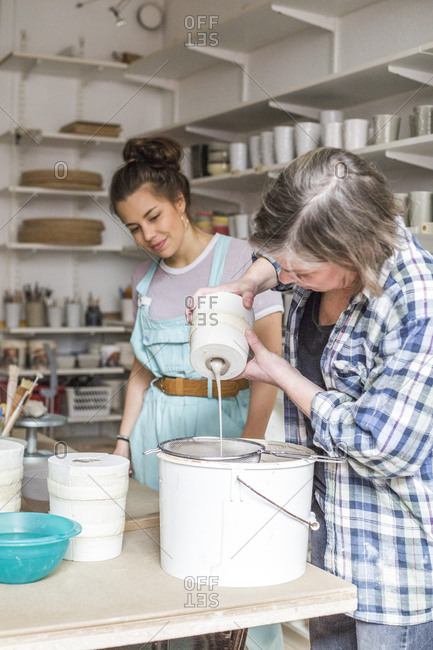 Young employee looking at mature female potter pouring clay from vase in strainer on bucket at workshop