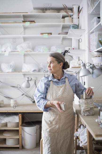 Senior female potter holding clay package while looking away in workshop
